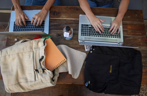 The two backpacks are laid flat on a table and two young people are typing away on their laptops next to the backpacks
