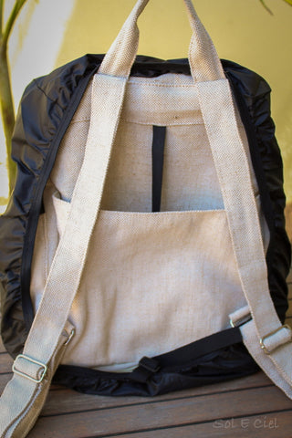 View of the back of the beige backpack when the rain shell is stretched out over the edges