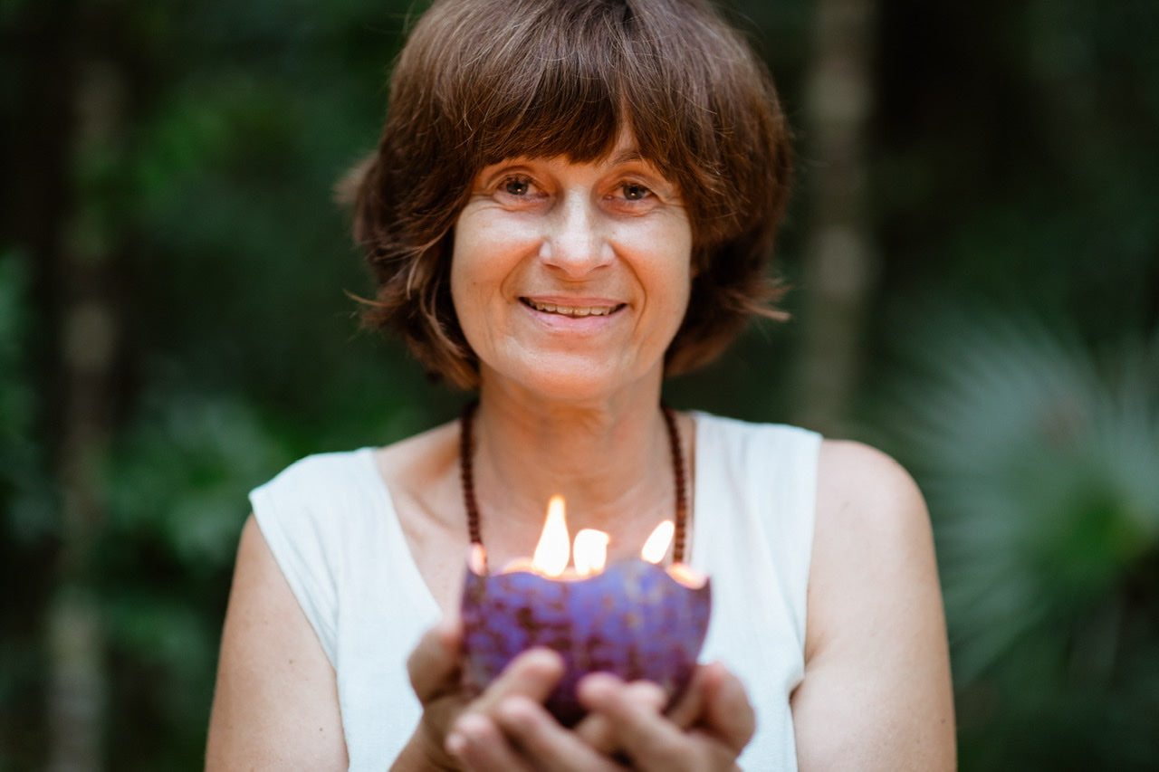 i am holding a five-wick purple candle while looking straight at the camera, on a dark green background of palm trees