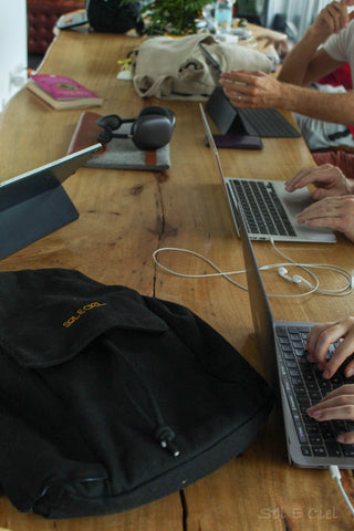 The black Tulum backpack is set on a table in an internet cafe
