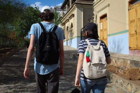 A young girl and a young man are walking in an exotic street while wearing Tulum backpacks