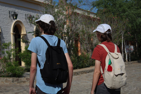 Two young men are wearing the backpacks while standing in an exotic street
