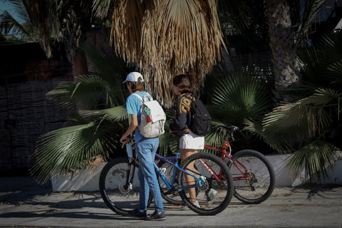 Two young people are pushing their bicycles on a sidewalk while wearing the backpacks