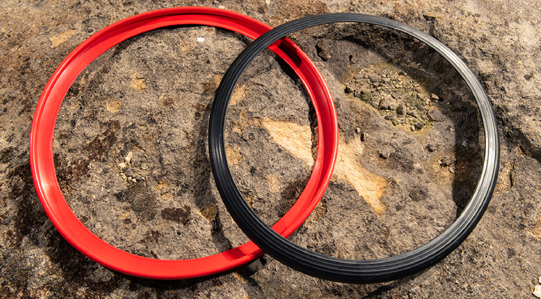 Overlapping black and red continuous rubber RIMFINITY product before fitting, on a natural stone background