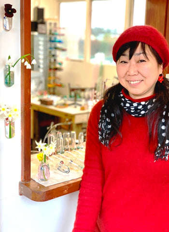 a person posing in front of handmade glass objects