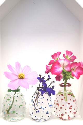 single flower in each of three vases on display