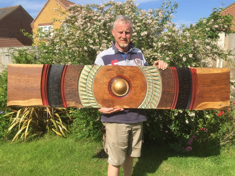 Darren Breeze holding a 5 foot by 1 foot wallhanging.