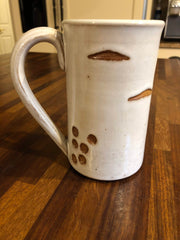 Ceramic mug with a face that appears as if it's made from a birch log.