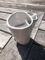 Mug that from overhead looks like a face with nostril handle and a tongue inside