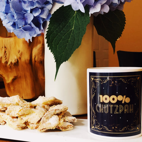 Kichel cookies shown on a platter next to mug of coffee and vase of flowers