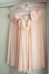 Three peach dresses hanging up together