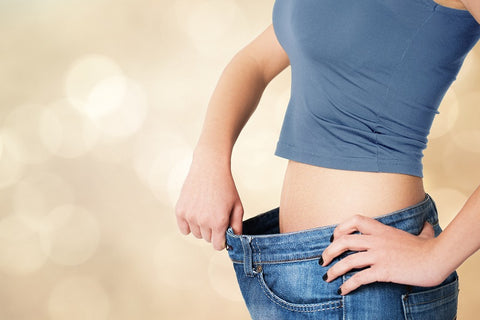 Woman in overly large jeans showing weight loss