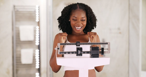 Woman Weighing Herself on Scale and Excited about Skinny Transformation