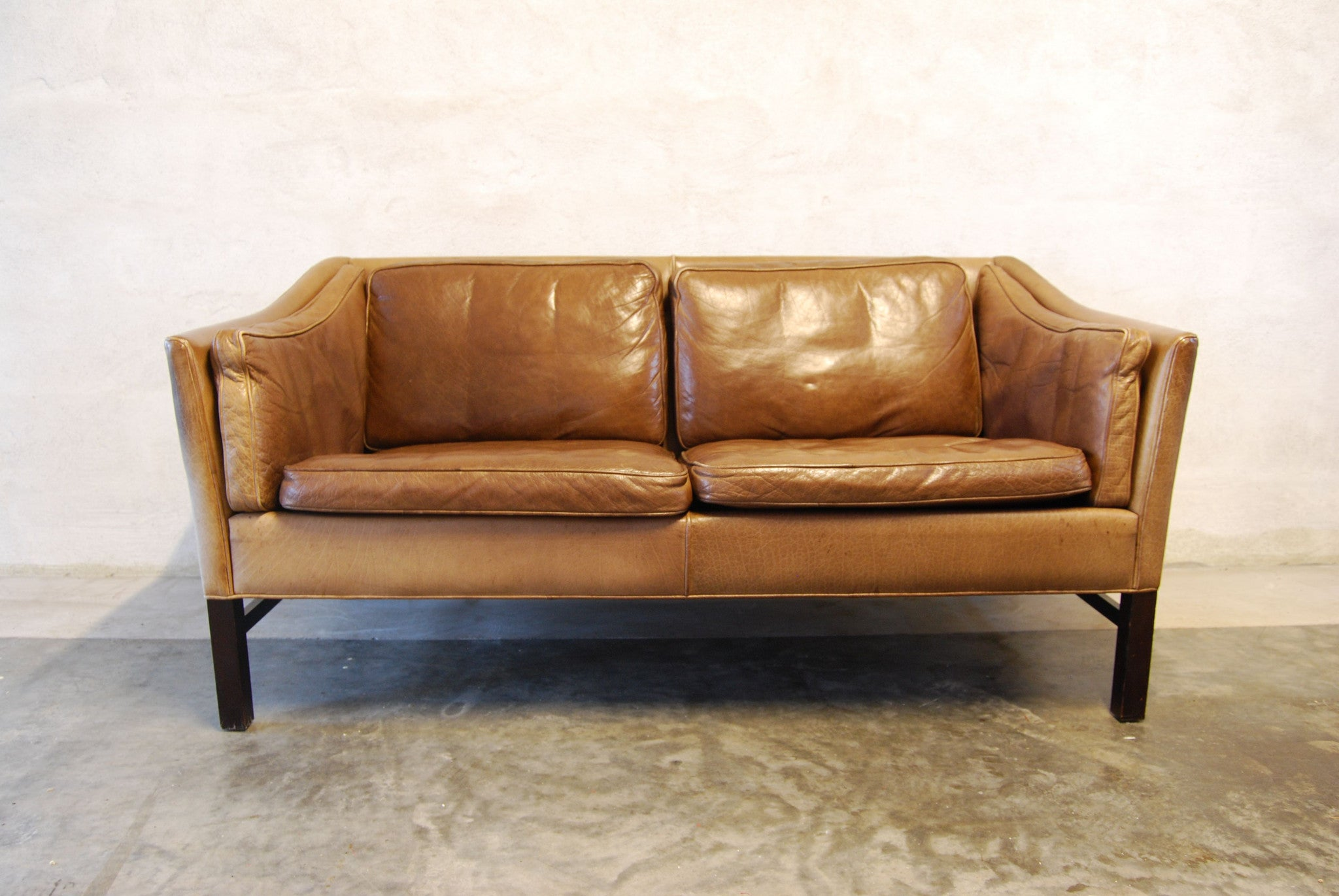 Two seat leather sofa with scalloped back