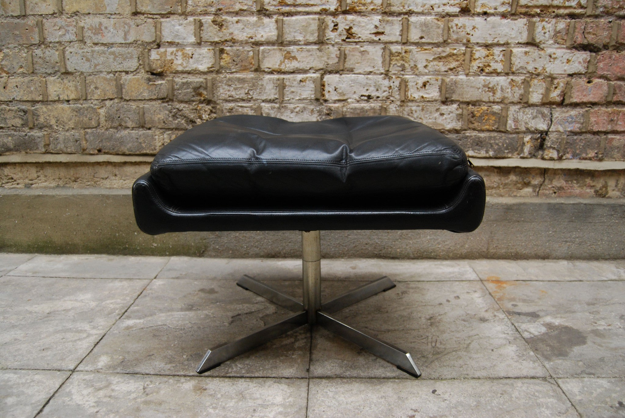 Black leather foot stool with chrome base