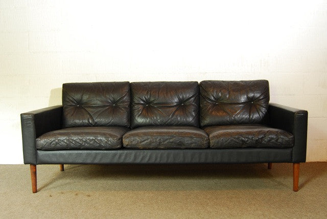 Black leather three seater on rosewood legs