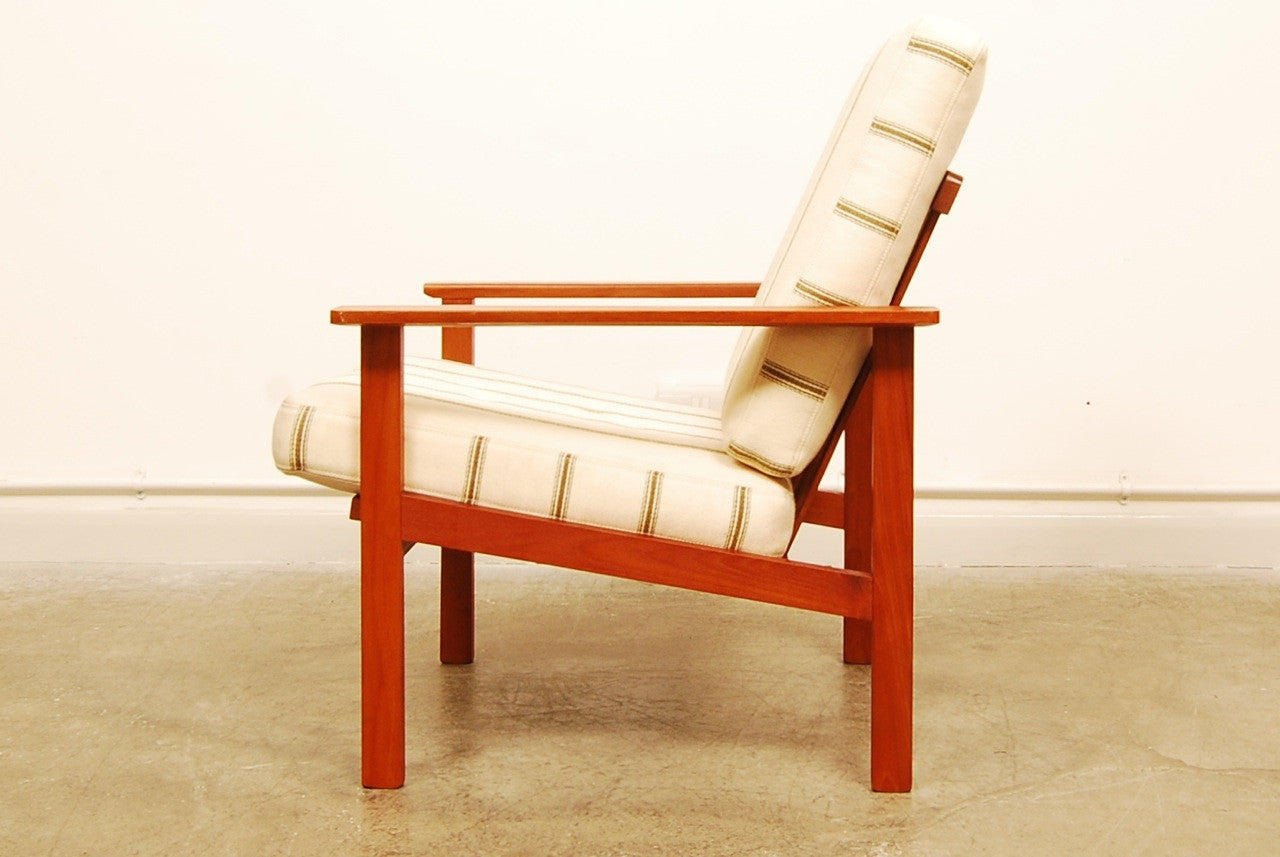 Teak lounge chair with cream cushions