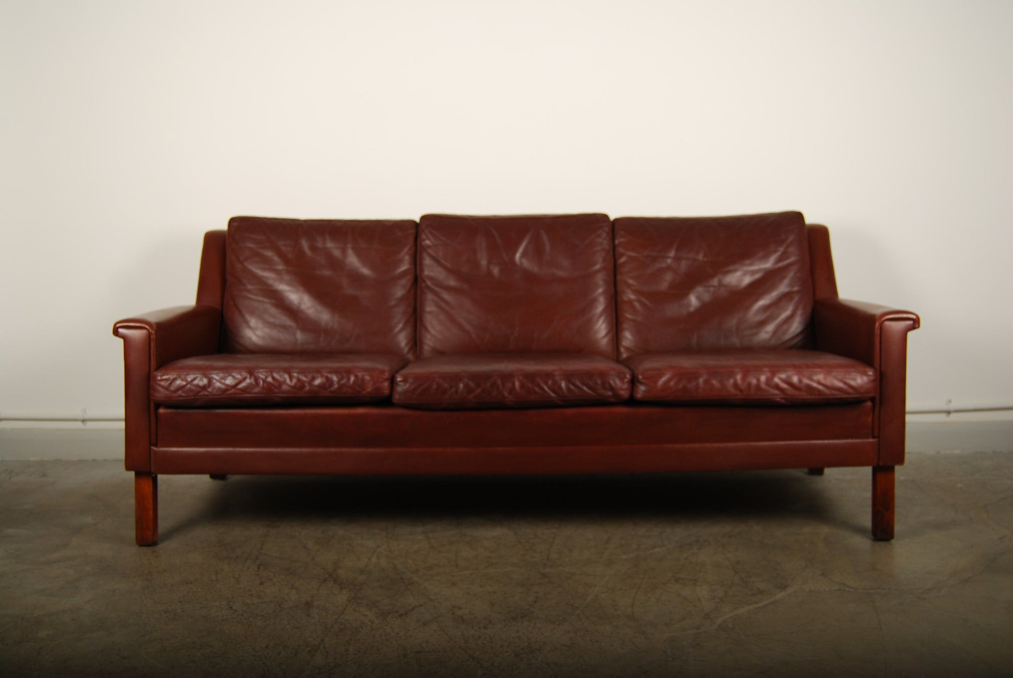 Leather three seater on rosewood legs