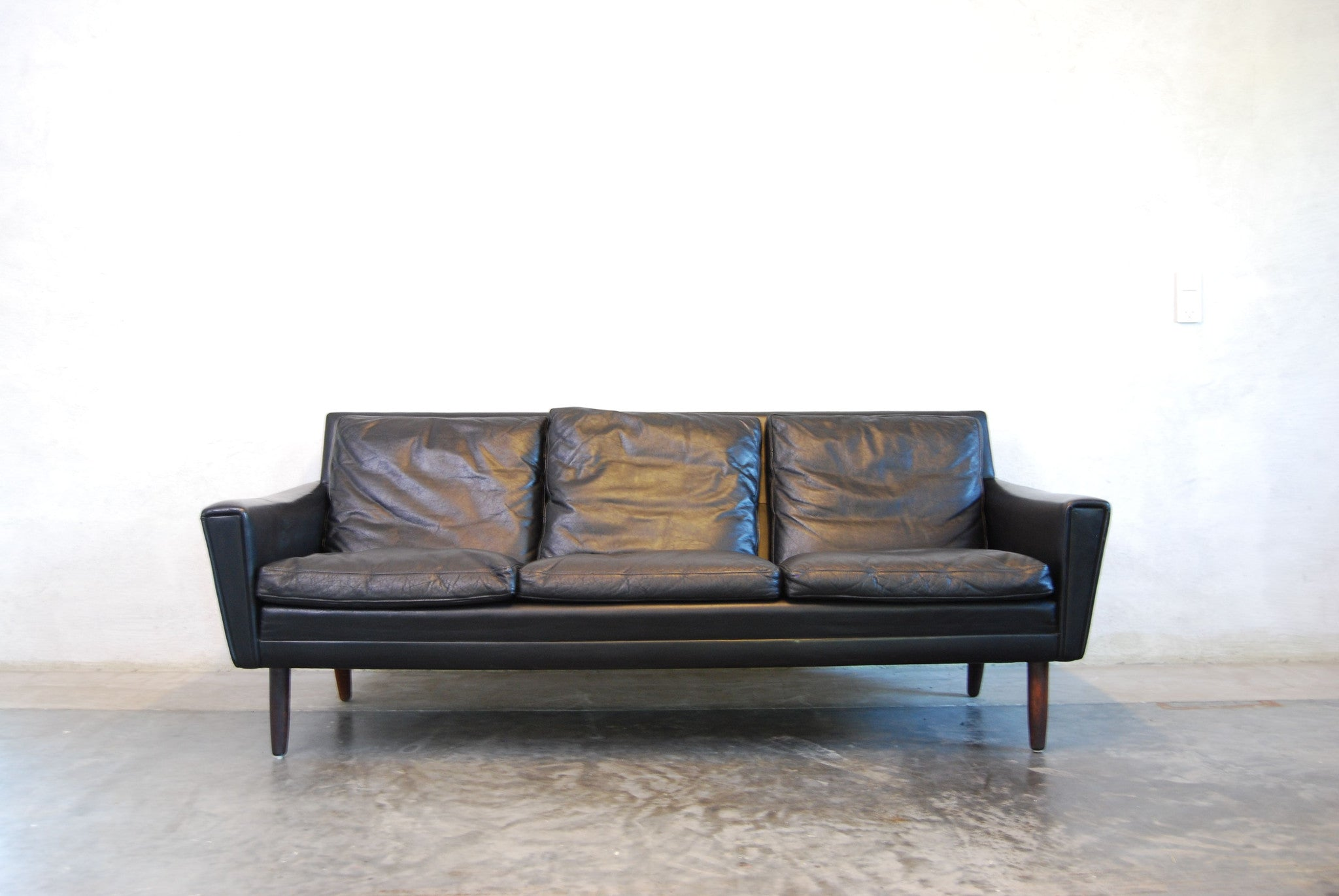 Three seat black leather sofa