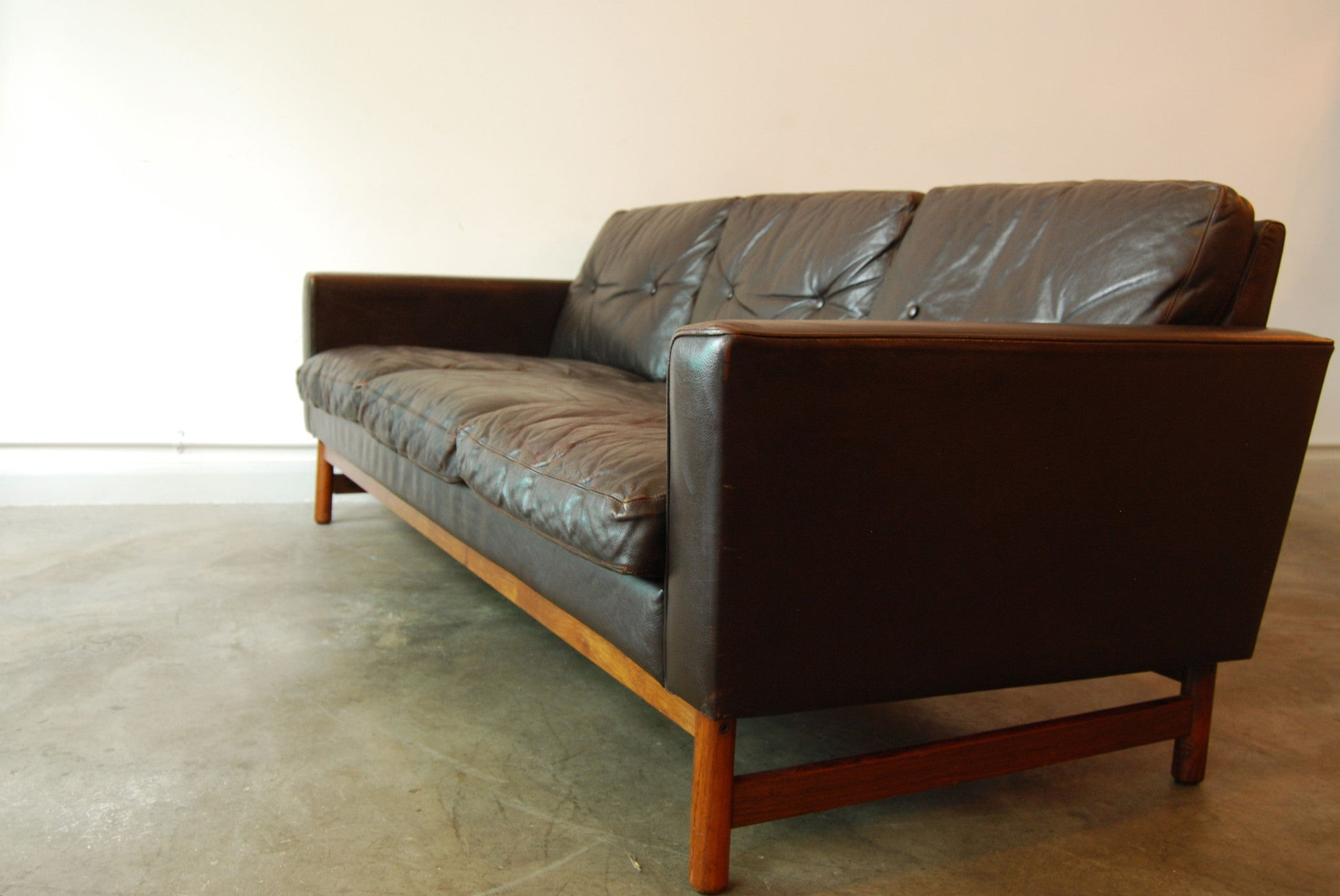 Three seat leather sofa on rosewood base
