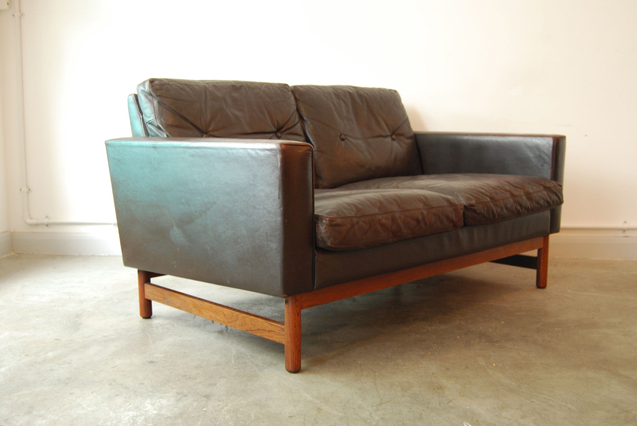Two seat leather sofa with rosewood base