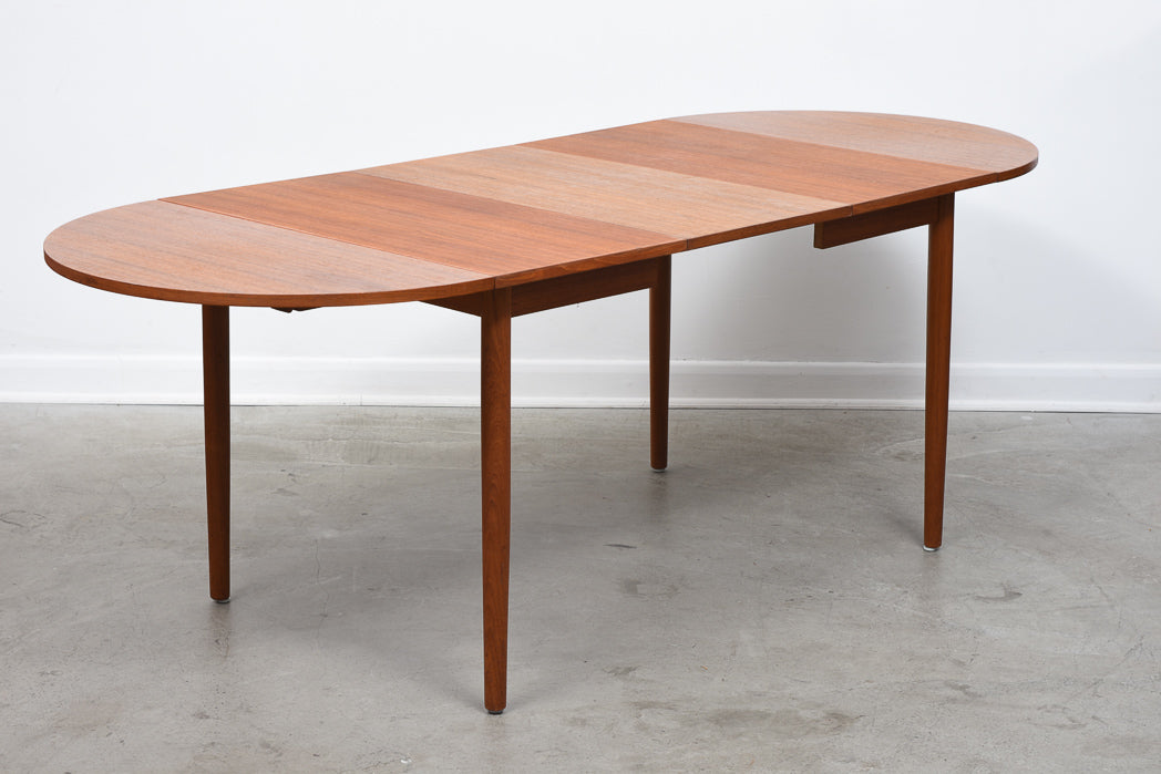 Extending dining table in teak with four leaves