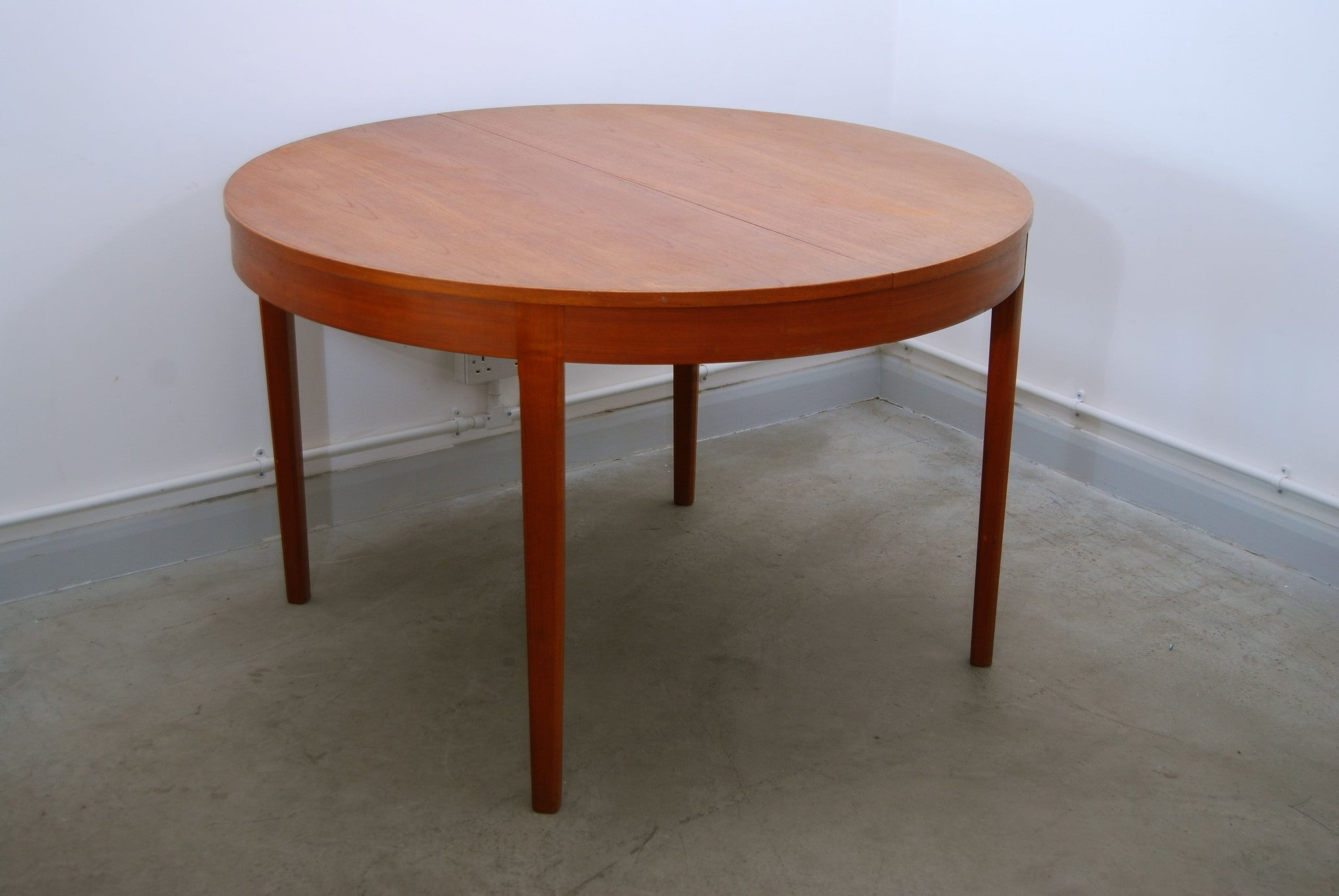 Round extending dining table in teak