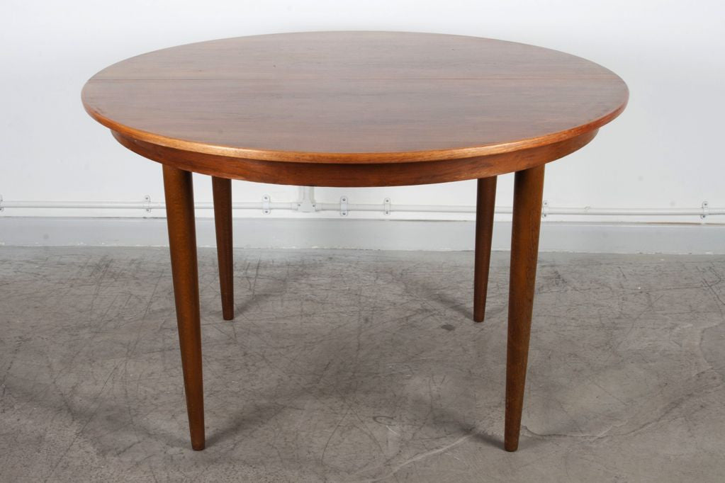 Round extending rosewood dining table