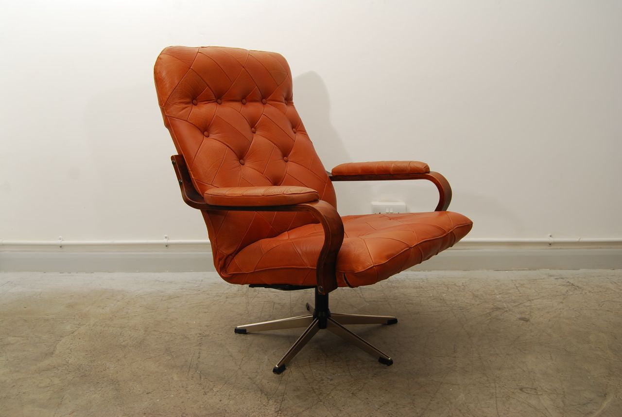 Cognac leather lounge chair on swivel base