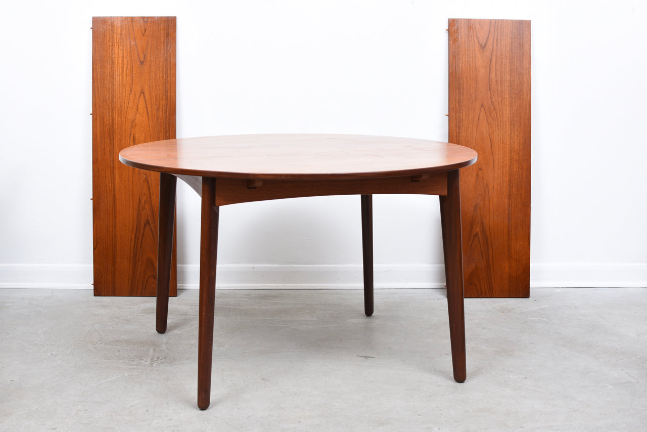 Extending dining table in teak on splayed legs