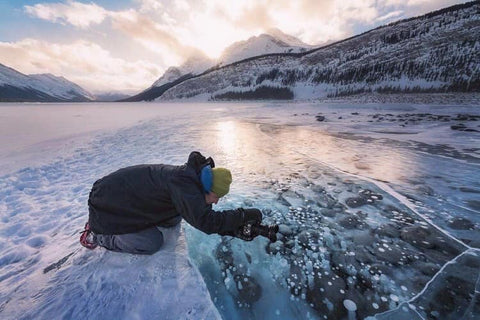 Peter Izzard up close and personal photographing ice bubbles in Alberta Canada.