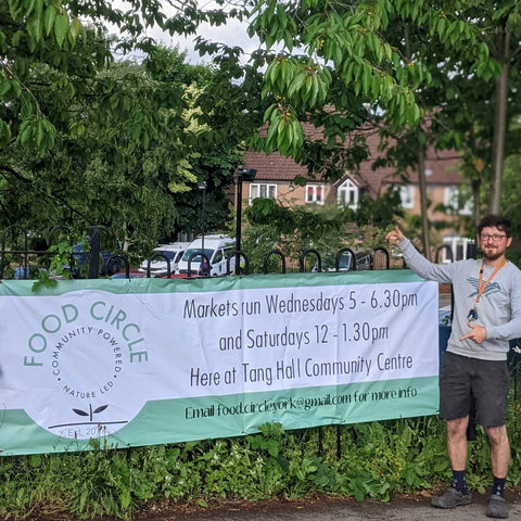Joe Fennerty standing next to the Food Circle York banner on railings at Tang Hall Community Centre