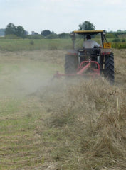 Small tractor turning hay