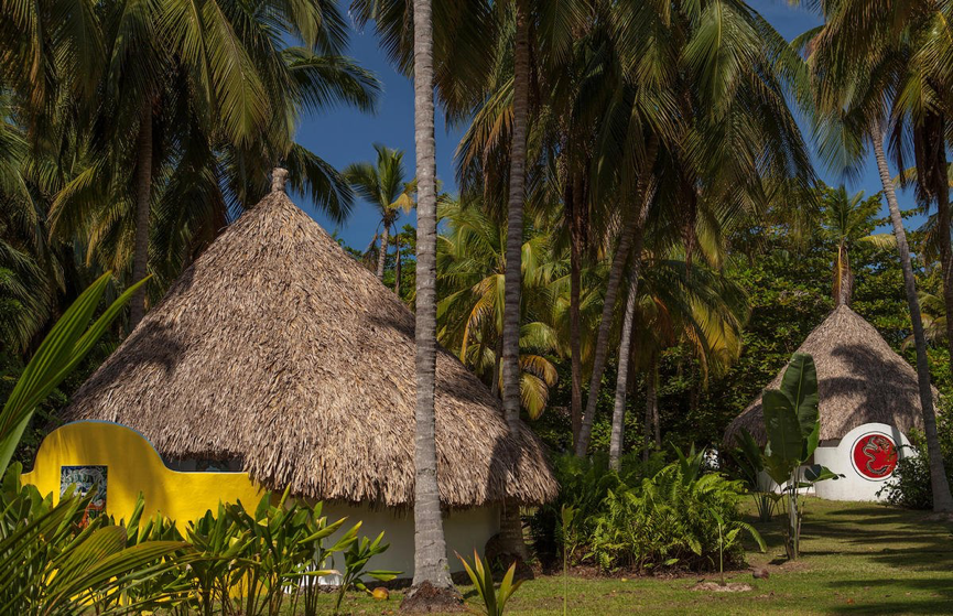 Huts with straw roofs surrounded by palm trees with a nice blue sky.