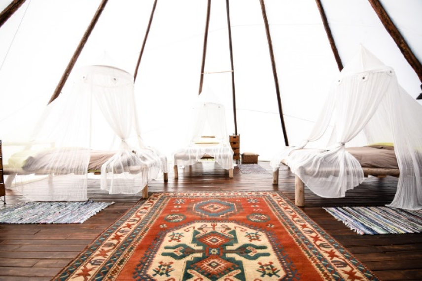 Large Tipi with three beds that have mosquito nets protecting them. There is also a nice large colorful rug which has tribal pattern placed on the wooden floor.