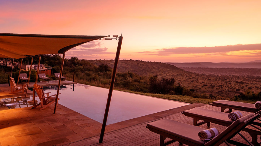 An orange and pink dusk light floods the this infinity pool which is surrounded by sunbeds and is situated on top of a mountain.