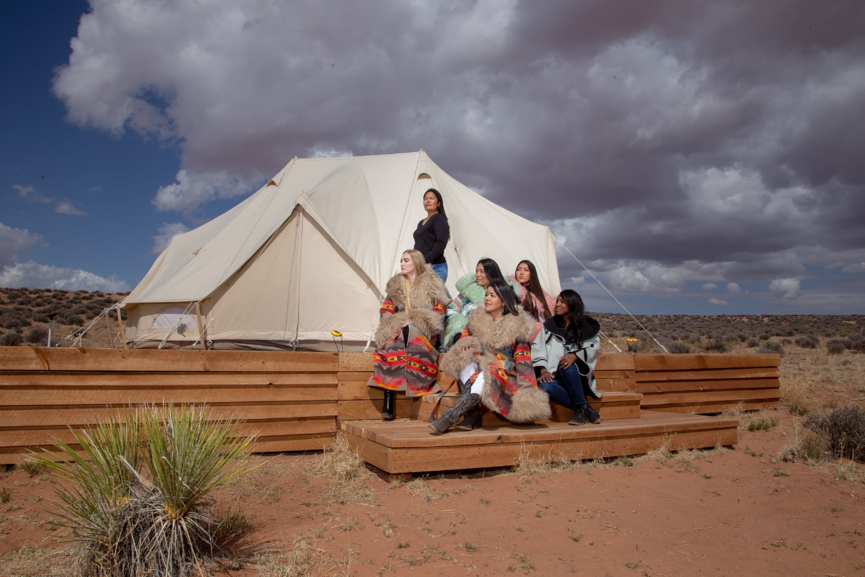 A group of women wearing Navajo patterned coats sit on a bench looking to the left outside a tent.