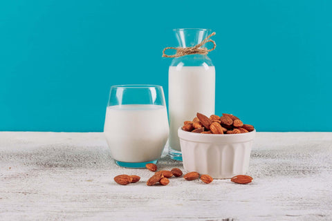 bottle-milk-with-glass-milk-bowl-almonds-side-view-white-wooden-blue-background