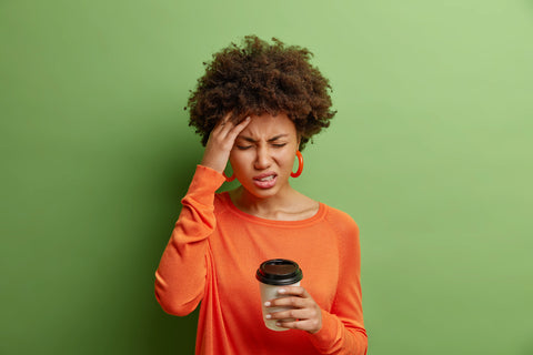 stressful-afro-american-woman-feels-terrible-headache-smirks-from-pain-closes-eyes-touches-temple-drinks-coffee-wears-casual-orange-jumper-isolated-vivid-green-wall