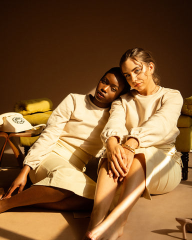 Two women sitting on the floor, wearing nude skirts and nude jumpers. Sunlight streams in through the window.