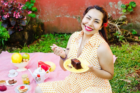 Smiling happy eating cake in yellow dress woman