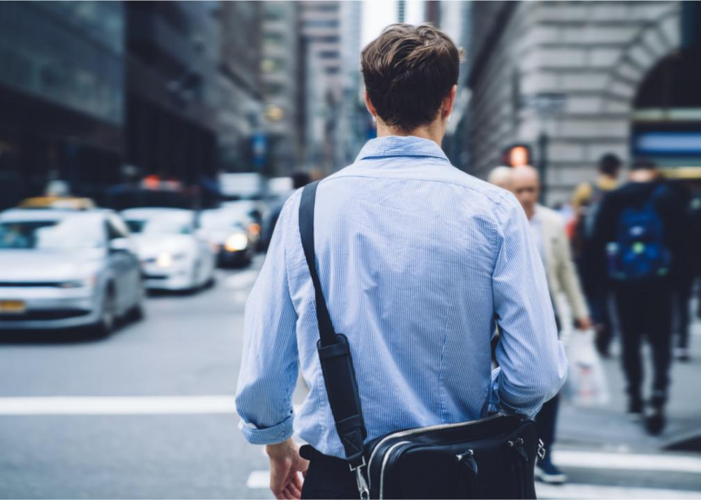 A man is walking to work and crossing a busy street (GaudiLab // Shutterstock)