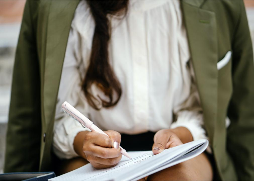 A woman is sitting down writing notes (mentatdgt // Shutterstock)