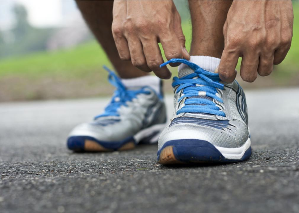 A man is bending over to tie his shoelace (Ekapong // Shutterstock)