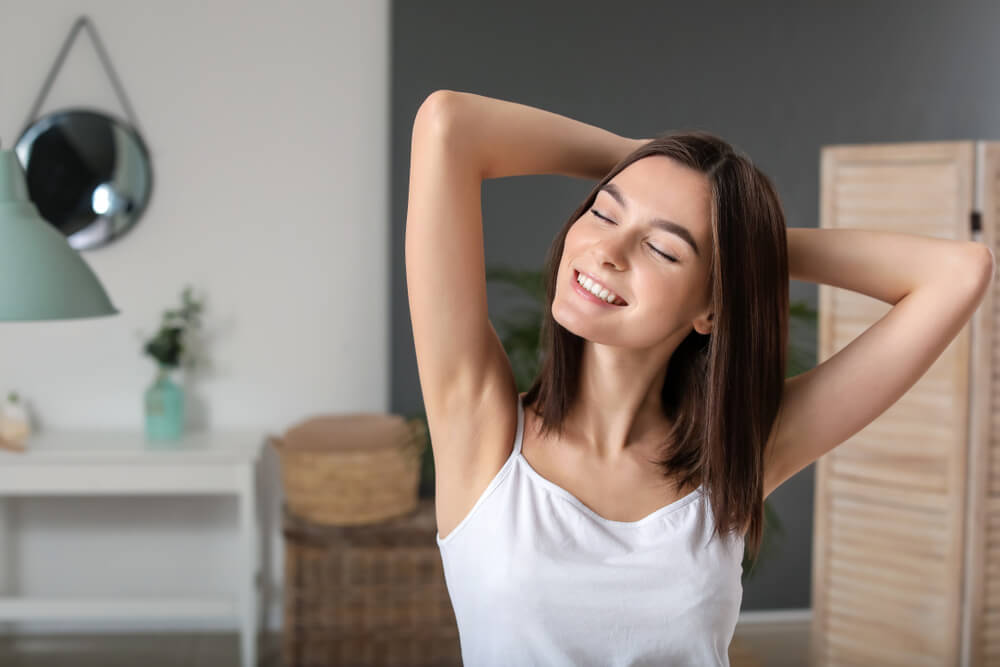 Natural antiperspirant for excessive sweating: A photo of a woman in the bathroom with her hands on her head.