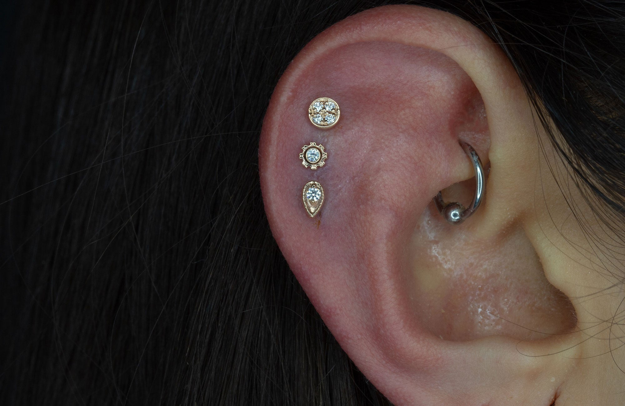 earlobe piercing with feather jewellery