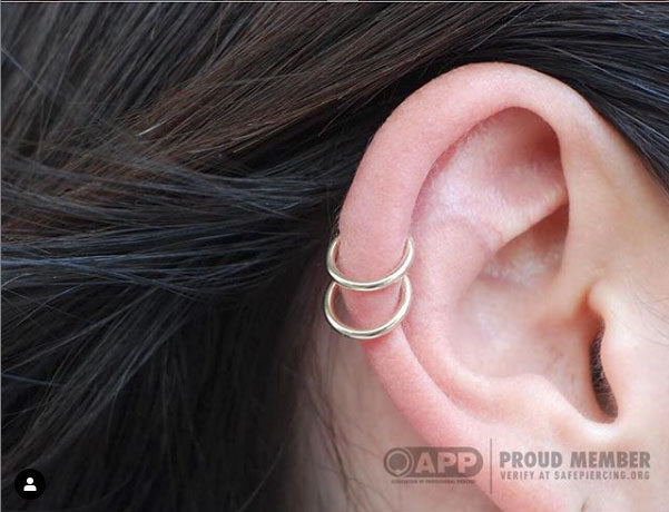 double helix piercing with gold ring