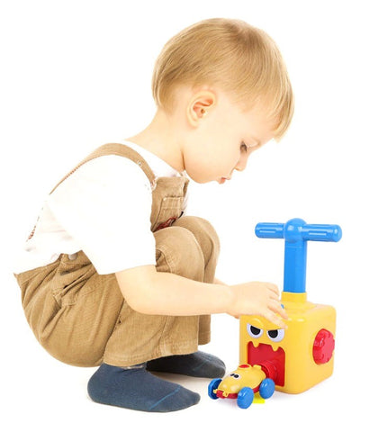 kid playing with balloon powered toy car - Sticky Balls Boutique