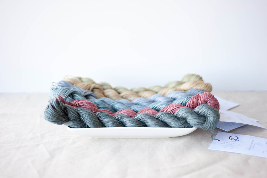 Skeins of colorful linen yarn lay in a white ceramic dish, sitting on a linen cloth