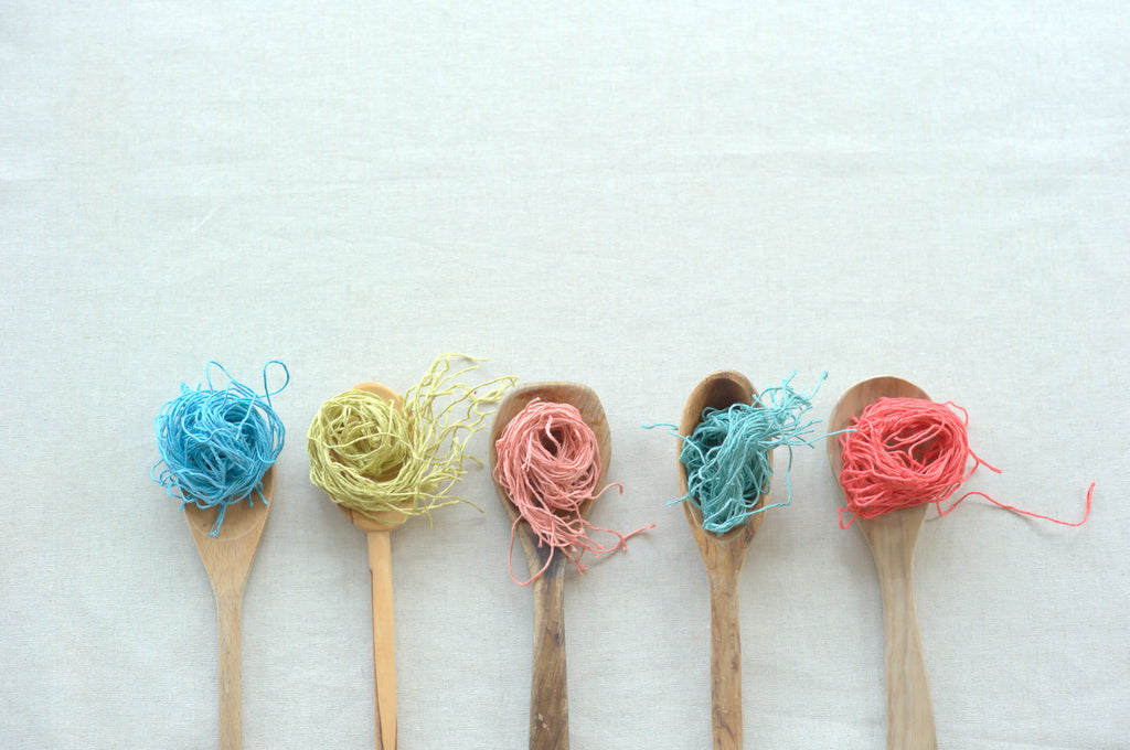 Five brightly-colored whorls of linen yarn rest in the bowls of five handmade wooden spoons